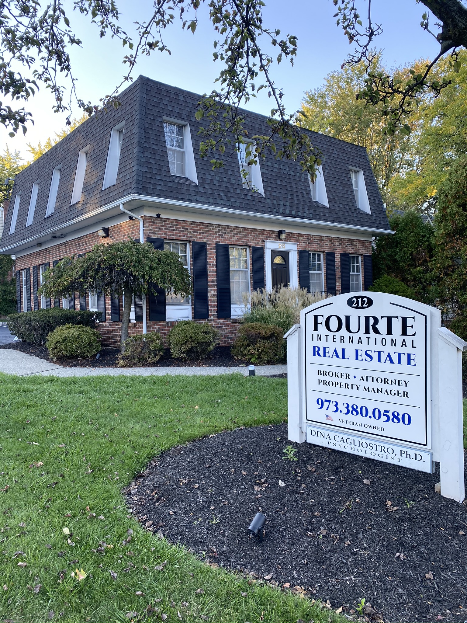 Fourte International Real Estate's Headquarters building in Essex County New Jersey with a sign on the front lawn advertising broker, attorney and property manager services
