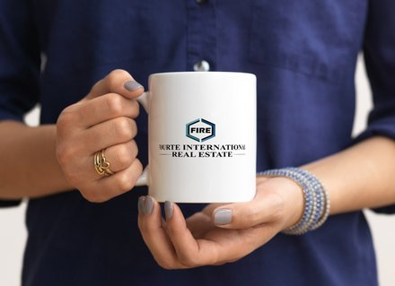 A New Jersey real estate agent holding a Fourte International Real Estate coffee mug